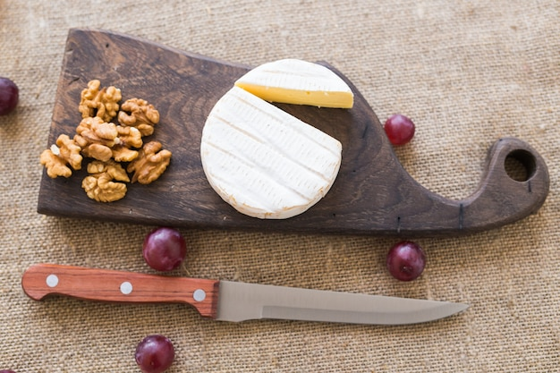 Queijo brie ou camembert com nozes e uvas em uma placa de madeira vista superior