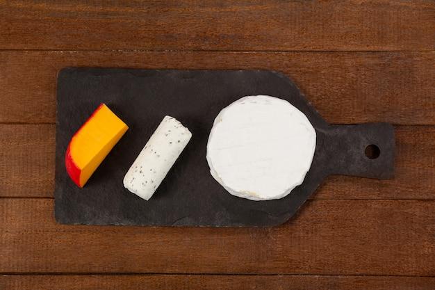 Queijo brie, queijo de cabra e queijo gouda na lousa
