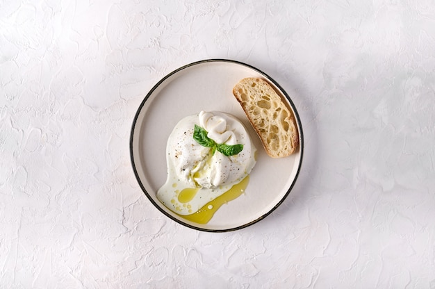 Queijo burrata italiano com pão ciabatta e azeite em chapa branca vista de cima cópia espaço