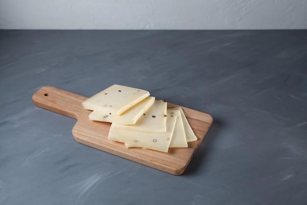Queijo caciotta italiano com pimenta preta. fatias na tábua de madeira.