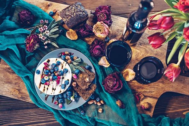 Queijo camembert com mirtilos, pão, nozes e vinho tinto, decorado com flores