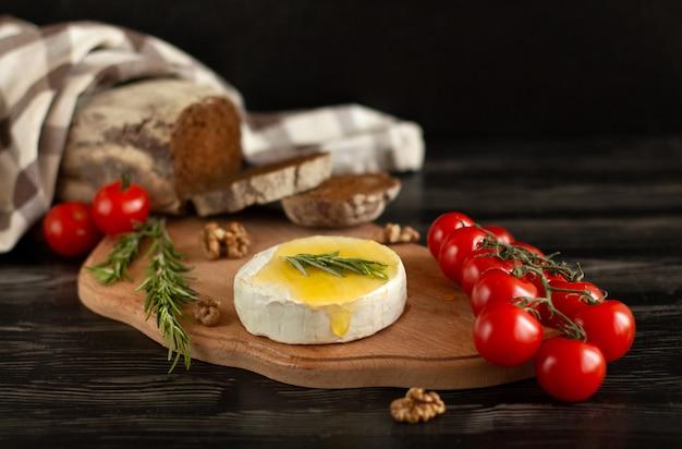 Queijo camembert com pão de centeio, nozes, mel, tomate cereja e alecrim em uma placa de madeira