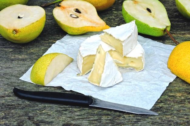 Queijo camembert com peras numa superfície de madeira.