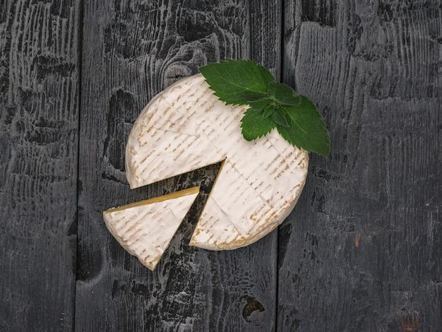 Queijo camembert com um pedaço cortado e folhas de hortelã em uma mesa de madeira.