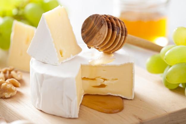 Queijo camembert com uvas, mel e nozes em fundo de madeira