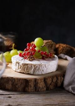 Queijo camembert com uvas, nozes e frutas com espaço de cópia