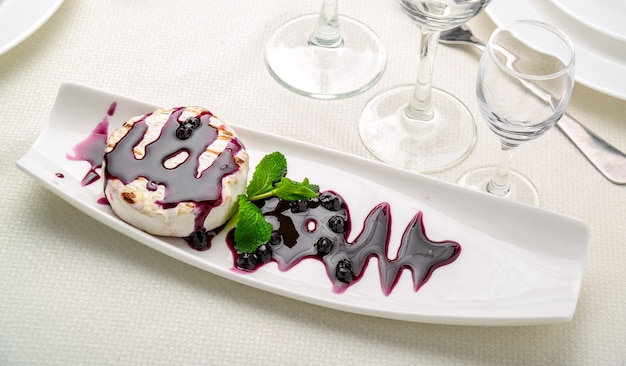 Queijo camembert cozido com molho de cranberry e hortelã na mesa.