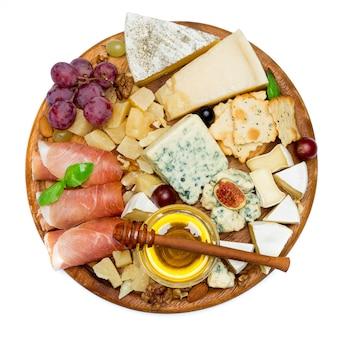 Queijo camembert e presunto com mel, figos, nozes na placa de madeira