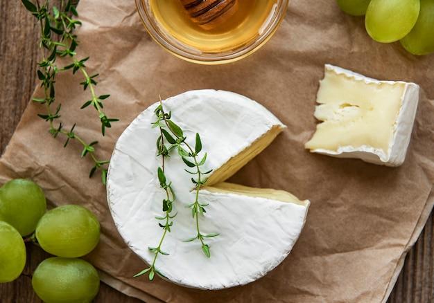 Queijo camembert e salgadinhos na velha mesa de madeira