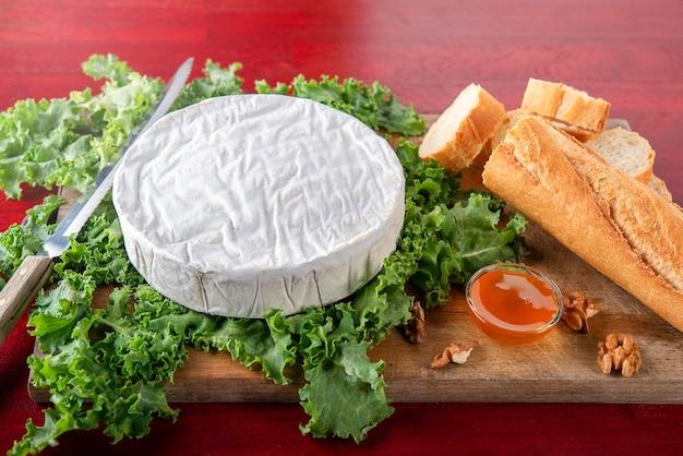 Queijo camembert em salade verde com tigela de mel e baguete de pão