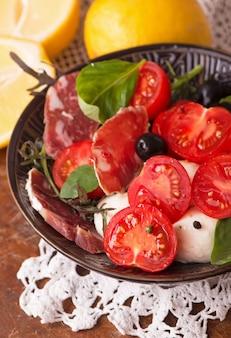 Queijo camembert redondo com tomate cereja e manjericão em um prato escuro