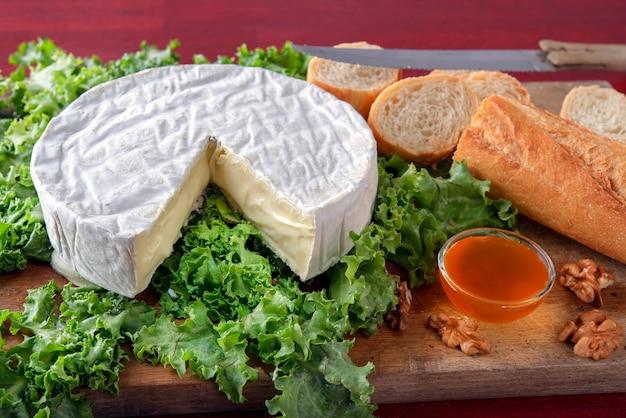 Queijo camembert rústico em tábua de madeira com salade verde com tigela de mel e baguete de pão
