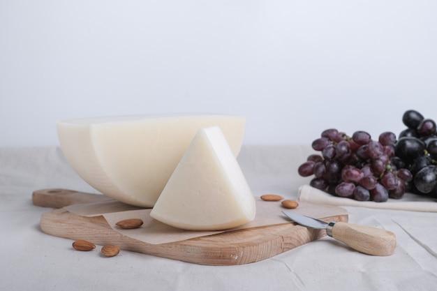 Queijo caseiro com uva vermelha na placa de madeira