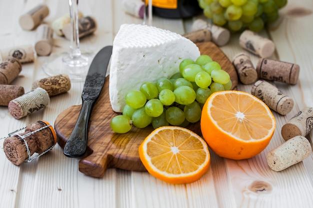Queijo caseiro com uvas e uma taça de champanhe