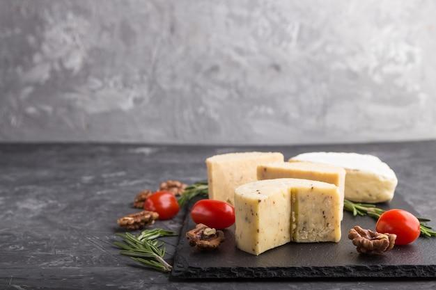 Queijo cheddar e vários tipos de queijo com alecrim e tomate em uma placa de ardósia preta em uma superfície de concreto preto