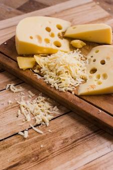 Queijo cheddar ralado e fatia de queijo emmental na tábua sobre a mesa