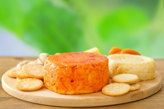 Queijo com biscoitos na superfície de madeira
