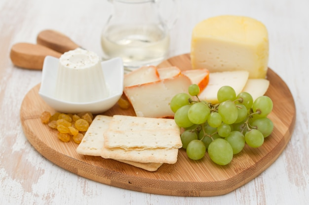 Queijo com biscoitos, uvas e vinho branco