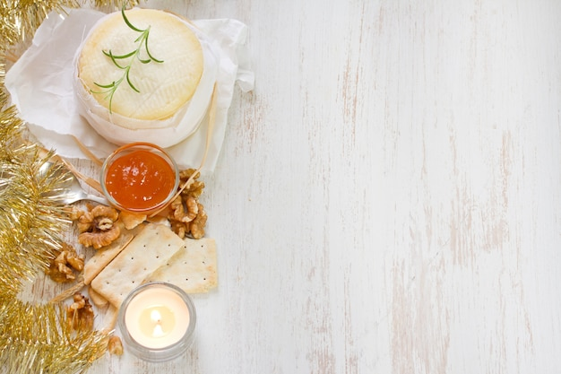 Queijo com geléia de abóbora e biscoitos na superfície de madeira branca