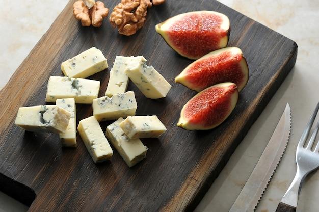 Queijo com mofo azul dorblu, algumas fatias de figos e nozes são servidos em uma tábua de madeira. há talheres nas proximidades.