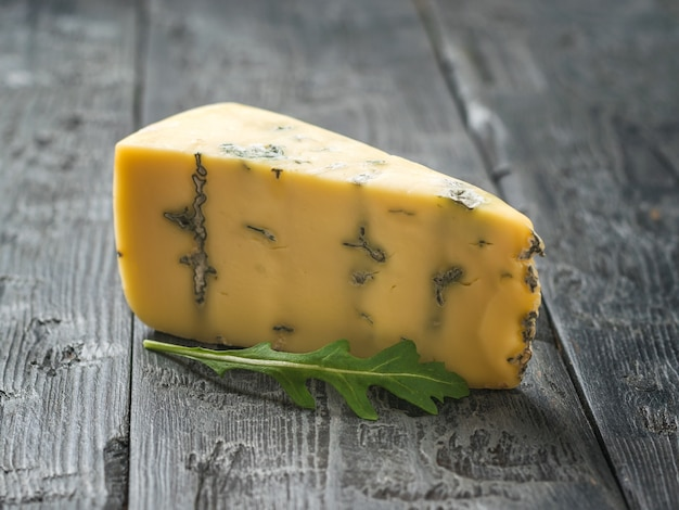 Queijo com mofo azul e rúcula em uma mesa de madeira. delicadeza de queijo. um molde útil