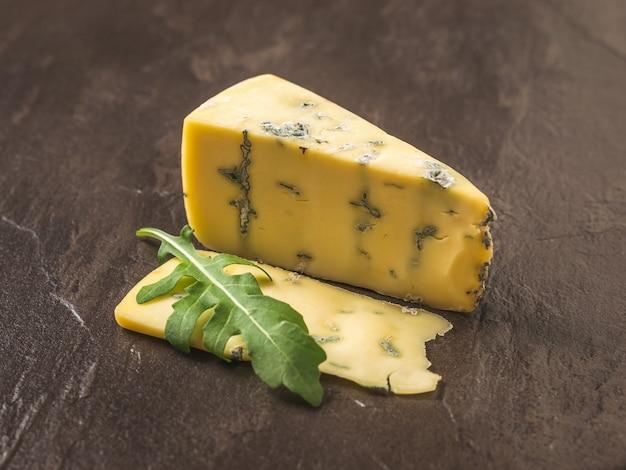 Queijo com mofo azul e um raminho de rúcula em uma superfície de pedra. delicadeza de queijo. um molde útil