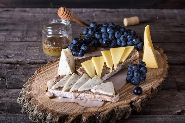 Queijo com uvas, pão, mel. queijo de cabra com ervas. placa de madeira natural. brusqueta.