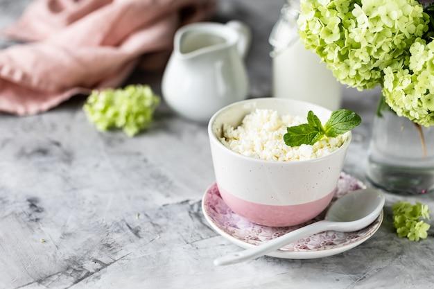 Queijo cottage café da manhã com mirtilos, creme, leite em uma mesa branca e um ramo de flores.