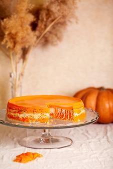 Queijo cottage caseiro e caçarola de abóbora com sementes de papoula e laranja em um suporte de vidro em cima da mesa com abóboras e juncos.
