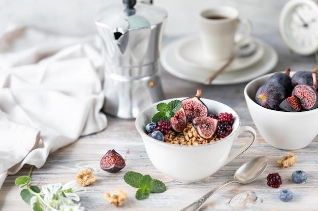 Queijo cottage com figos, frutas, mel. xícara de café e cafeteira. café da manhã. mesa de madeira.