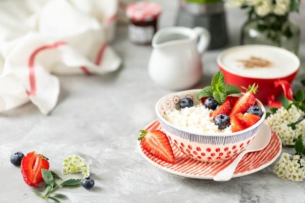 Queijo cottage com frutas, geléia, morangos frescos e uma xícara de café com creme no café da manhã.