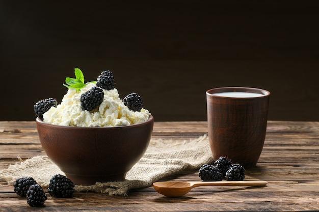 Queijo cottage de produtos lácteos e leite na tigela de cerâmica marrom com colher em madeira