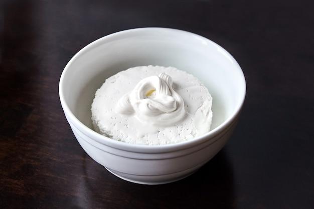 Queijo cottage em uma tigela de cerâmica branca coberta de creme de leite na mesa de madeira escura. coalhada - laticínios