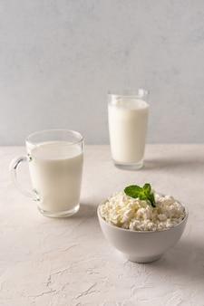 Queijo cottage em uma tigela, kefir em um copo e leite em uma xícara sobre um fundo claro.