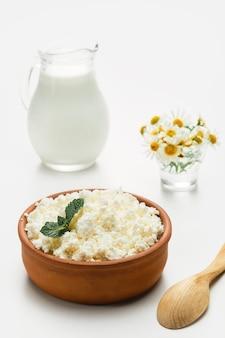 Queijo cottage em uma xícara rústica de cerâmica, ao lado de uma colher de pau e uma jarra de leite. close-up, foco seletivo, fundo branco brilhante. requeijão macio, comida natural saudável, comida de dieta completa