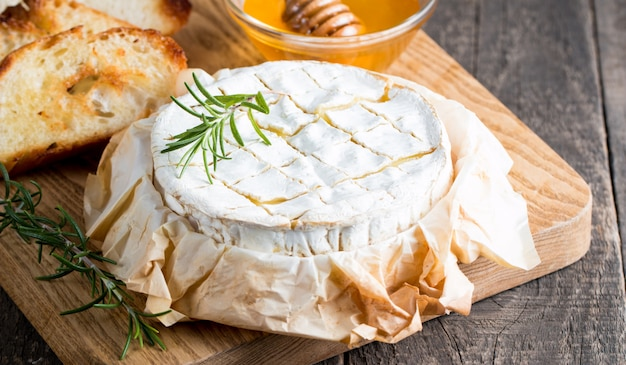 Queijo cozido do camembert ou do brie em uma placa de madeira.