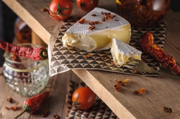 Queijo creme brie bonita servindo em um carrinho de madeira com tomate cereja e pimentão