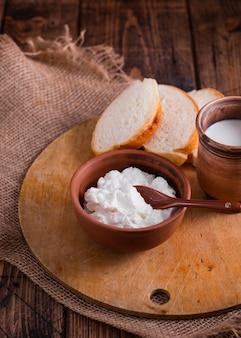 Queijo cremoso de alto ângulo e pão sobre uma mesa