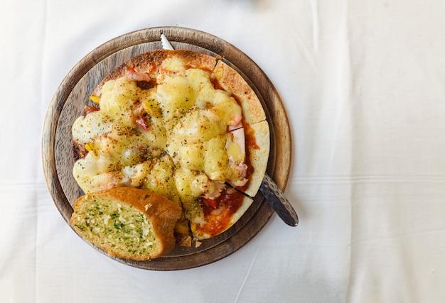 Queijo crocante de pizza fina com salmão, presunto, bacon na bandeja de madeira