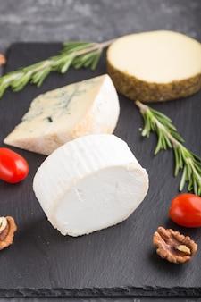 Queijo de cabra branco e vários tipos de queijo com alecrim e tomate em uma placa de ardósia preta em uma superfície de concreto preto