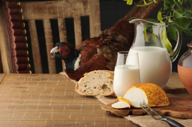 Queijo de cabra com condimentos, pão e jarro de leite na tabela de madeira contra o contexto da caça.