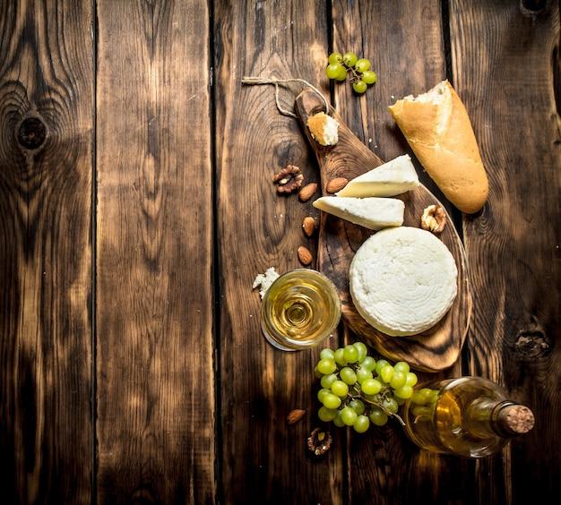 Queijo de cabra com vinho branco e nozes. em uma mesa de madeira.