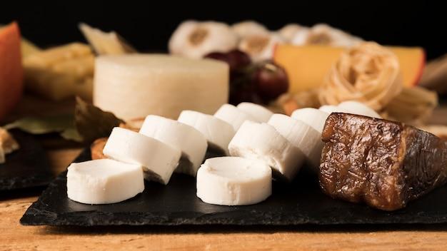 Queijo de cabra e queijo brunost na ardósia preta da rocha