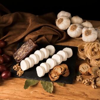Queijo de cabra fresco na bandeja de ardósia com fatias de pão e noz perto de macarrão cru e alho bulbos