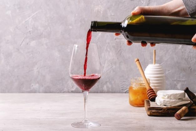 Queijo de cabra servido com mel e garrafa de vinho tinto sobre fundo branco de textura. copie o espaço
