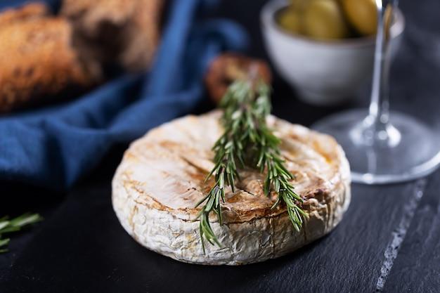 Queijo de camembert assado com alecrim, azeitonas e pão, close up