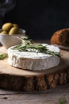 Queijo de camembert assado com alecrim, azeitonas e pão, foco seletivo