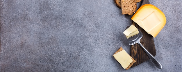 Queijo de gouda holandês delicioso com fatias do queijo, pão do multigrain e faca especial na placa de madeira velha.