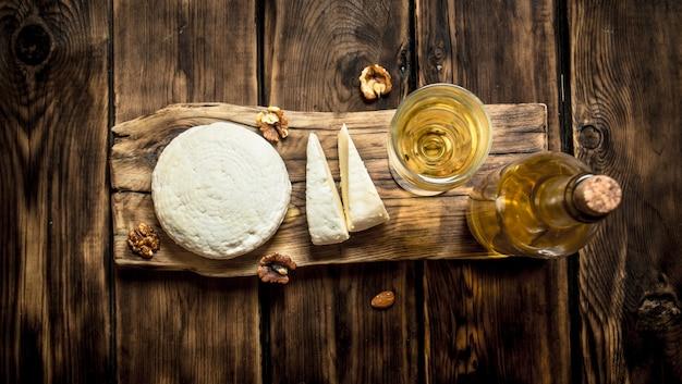 Queijo de ovelha com vinho branco e nozes. em uma mesa de madeira.