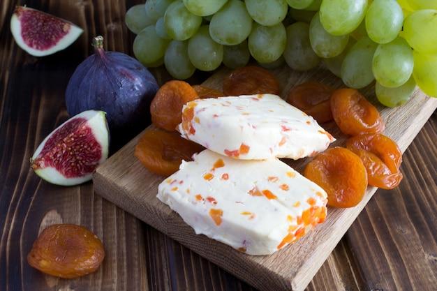 Queijo de pasta mole com damascos secos e frutas na tábua de madeira